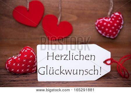 Label With German Text Herzlichen Glueckwunsch Means Congratulations. White Label With Red Textile Hearts. Retro Brown Wooden Background.