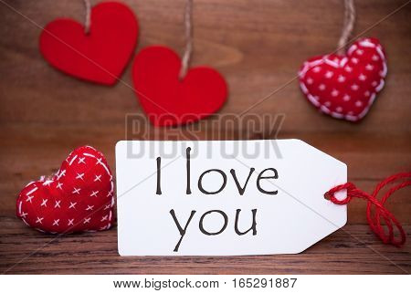 Label With English Text I Love You. White Label With Red Textile Hearts. Retro Brown Wooden Background.