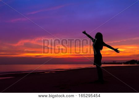 Silhouette Of Woman With Hands Up While Standing On Sea Beach At Sunset