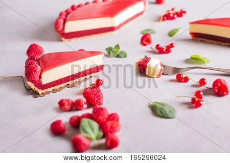 Tart pie cake with jellied and fresh raspberry on the light concrete background. Top view. Slice of cake