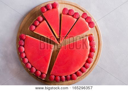 Tart pie cake with jellied and fresh raspberry on the light concrete background. Slice of cake