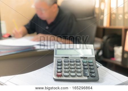 Dirty old calculator on office background and man working.