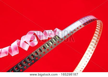 SMD components on a black plastic carrier tape with red background. White cover tape opens Christmas ribbon style.