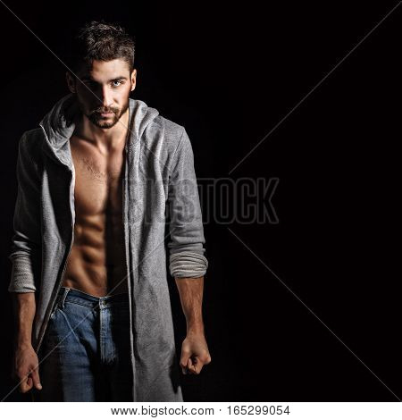 Man in sweatshirt and jeans. Piercing eyes. Husky eyes. Dramatic portrait in sporty style. Men's strength.