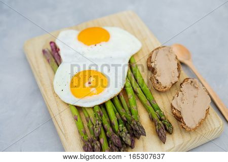 Breakfast Fried eggs with asparagus a on a wooden board and svetdom gray background. View from above