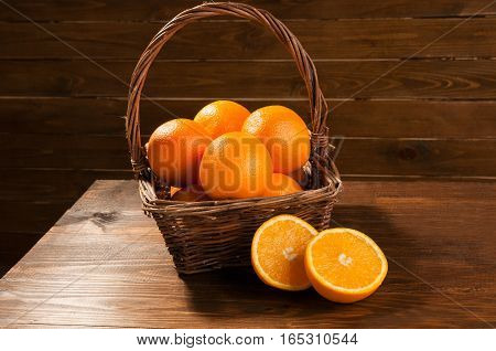 Oranges in a basket on a wooden background