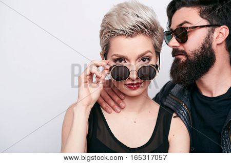 Hipster Beautiful Woman With Blond Short Hair. and her boyfriend. Modern couple with Stylish haircut and Hairstyle wearing black sunglasses. Professional Makeup.
