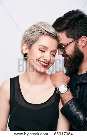 Close-up vertical portrait of fashion couple in love in stylish street clothes, wearing leather black rock n roll look