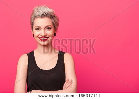 Pretty young woman with short blond hair wearing black t-shirt smiling against a pink background with copy space. Happy hipster girl close-up portrait