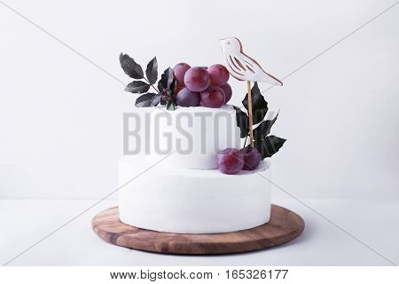 White two-tiered cake decorated with a bird grapes and leaves on a light background