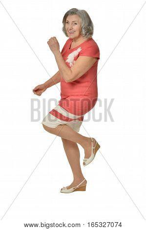 beautiful senior woman in pink dress posing on white background
