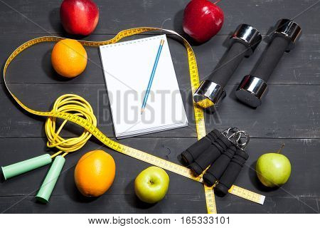 dumbbells and fruits, fitness background on a black wooden background