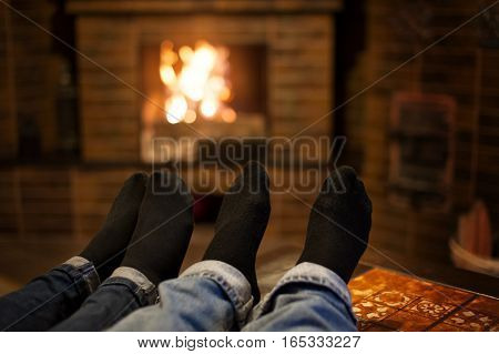 Close up of romantic legs in socks in front of fireplace.