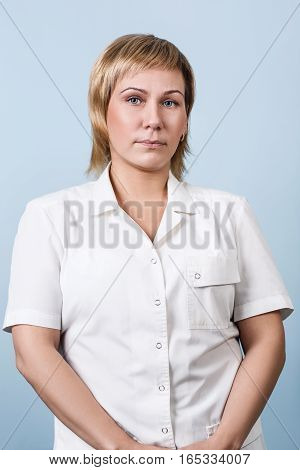 Smiling medical woman doctor standing over blue background