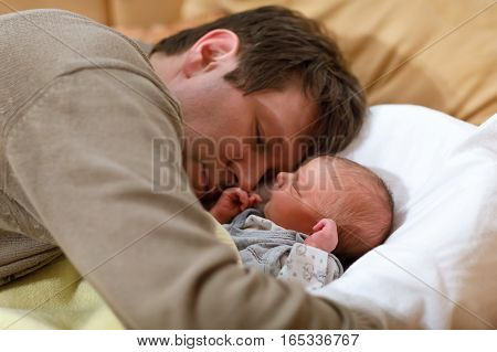 Middle aged father giving kiss his newborn baby daughter. Young dad hugging and cuddling with baby girl at home. Happy parenthood, carefree childhood, family, love. Cute adorable baby sleeping