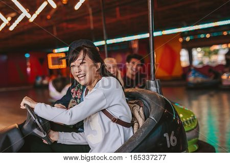 Happy young girl driving a bumper car with friends in background at amusement park