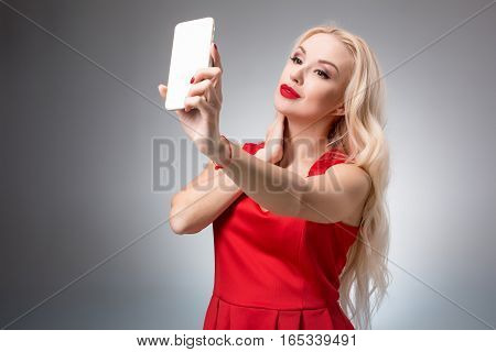 Portrait of a Beautiful successful blonde doing selfie in a red dress on a light background