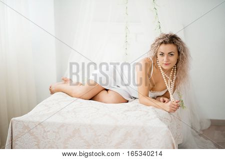 Curly Blonde Girl In A White Silk Gown Boudoir Robe On Bed.