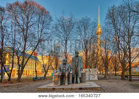 BERLIN GERMANY - 27 NOVEMBER 2016: Marx and Engels statue in Marx Engels Forum in Alexanderplatz with the TV tower in the background