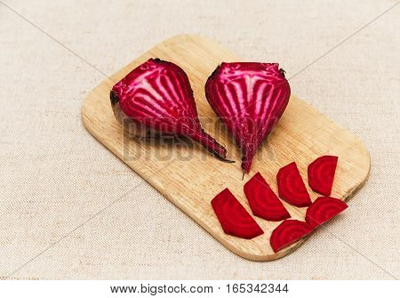 Red fresh beet with cut pieces on the rough tablecloth.Vegetables