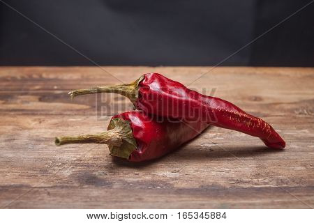 Two red peppers chilli on the wooden table