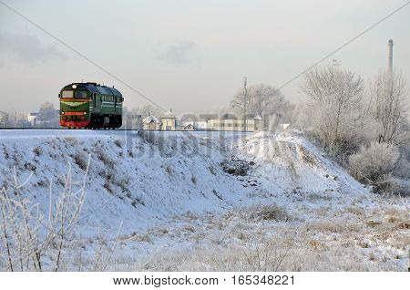 Riding old locomotive on the background of winter landscape of the village.