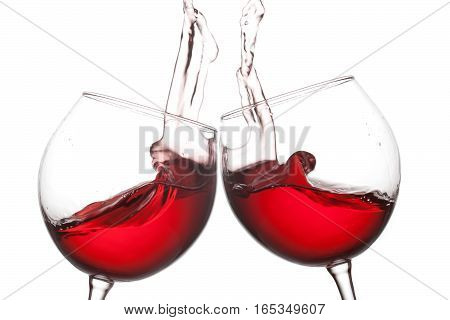 Two red wine glasses and splashing flow on white background. Celebration party concept photo. Macro view