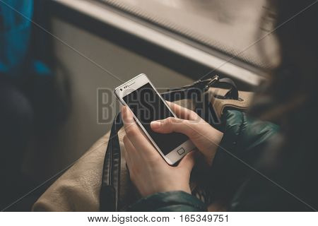 Close up view on the hands of a young woman holding a smart phone tapping the blank screen. Girl using device in a bus