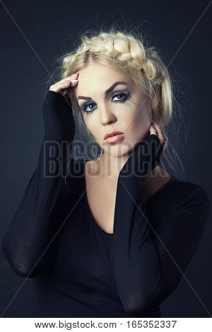 Portrait of a beautiful blonde woman with stunning eyes over black background. Beauty, fashion. Make-up.
