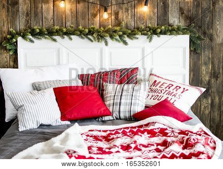 bed in the bedroom with pillows blanket decorated Christmas tree on the background of wooden wall