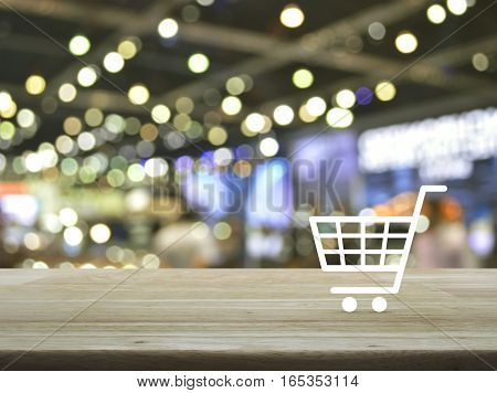 Shopping cart icon on wooden table over blur light and shadow of shopping mall Shop online concept