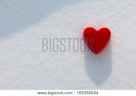 Lonely red heart in the snow with sunshine