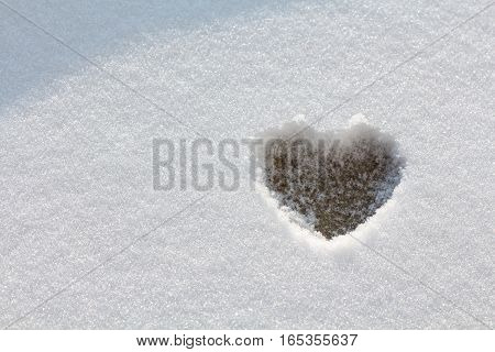 Heart form in the snow with sunshine