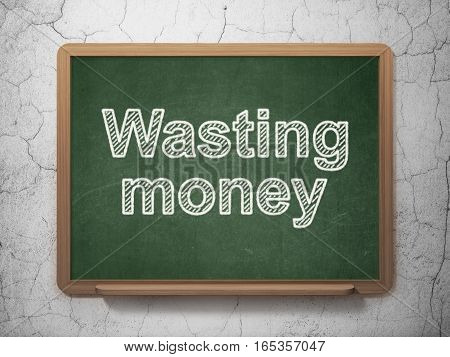 Currency concept: text Wasting Money on Green chalkboard on grunge wall background, 3D rendering
