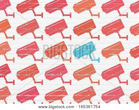Safety concept: rows of Painted red cctv camera icons around blue cctv camera icon on White Brick wall background
