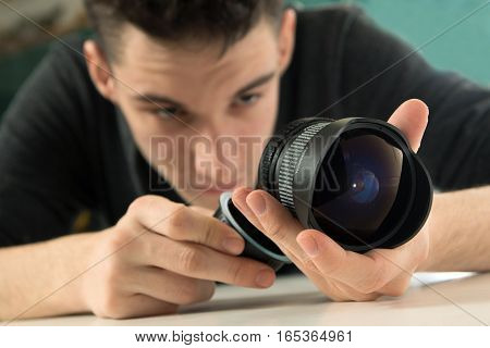 Young photographer checking dslr fisheye camera lens