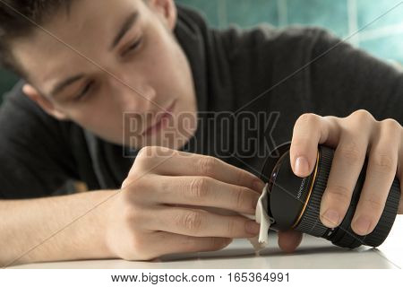 Young photographer cleaning dslr fisheye camera lens