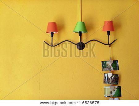 Tres lámparas decorativas con soporte de hierro en la pared amarilla.