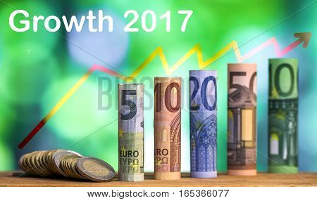 Five ten twenty fifty and one hundred euro rolled bills banknotes with euro coins on ggeen blurred bokeh background. Growth 2017 concept.