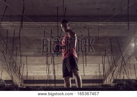 Young muscular built athlete working out with a dumbbell lifting weights in an abandoned building