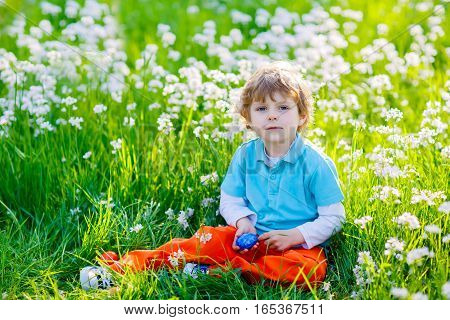 Cute little kid boy having fun with traditional Easter eggs hunt on warm sunny day, outdoors. Celebrating Easter holiday. Toddler finding, colorful eggs in green grass. Old German tradtiton