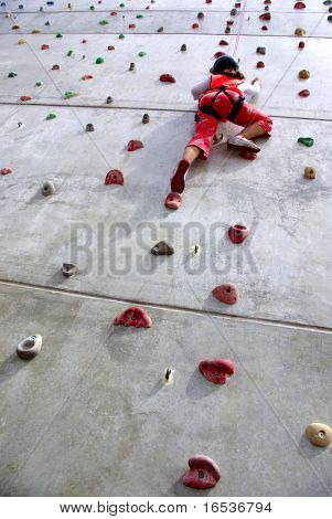 Youngster's effort in climbing a wall to reach the top.