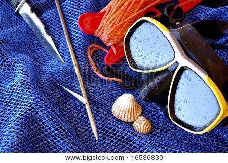 Detalles de buceo y pesca submarina del engranaje sobre una bolsa de red de pesca azul