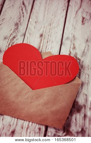 Envelope with Red paper Heart Valentine card vintage toned.