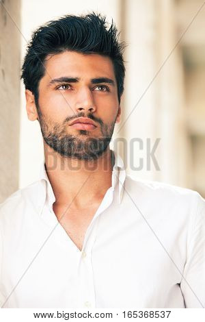 Handsome and stylish young man. Hair and beard fashionable. A beautiful young Italian man is outdoors. He is leaning against a marble wall. He wears a white shirt. Hair and black beard.