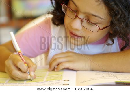 Concentrated young girl doing her school home-work.