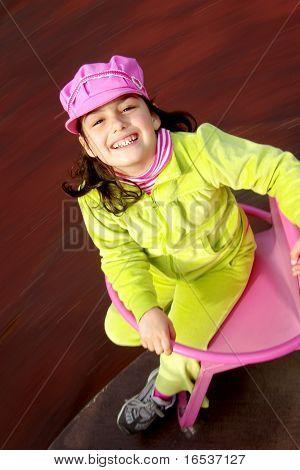 Lächelnd happy Child in einem Park spielen in ein spinner