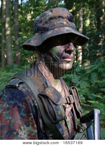 Camouflage soldier in woodland