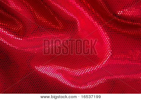 Red fabric background with shining little sequins