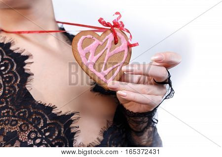Female hands in black lace gloves hold heart shaped gingerbread cookie with red ribbon on neck against bust in black transparent lace dress incognito close up. Valentine's day and love concept